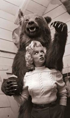 Actress Marilyn Monroe poses in front of a stuffed grizzly bear at the Luxton Indian Trading Post in Banff, Canada.