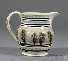 Early 19th century, baluster form jug with dark brown, blue, and green rouletted bands flanking a wide gray-blue band with black dendritic devices, extruded handle with leaf terminals, (rim repair, small hairlines), ht. 7 1/4 in.  green roulett...