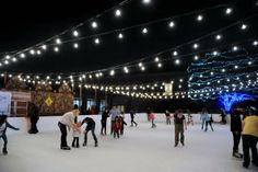 Families and friends try their best to stay balanced on the slick ice rink at the grand opening of Sparkle located in the Hilton Anatole gar...