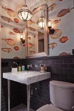This small guest bathroom received a bold design choice: fish patterned wallpaper. The whimsical wallpaper paired with black matte-finished tiled surfaces creates a moody interior. wallpaper bathroom Powder Room With Fish Patterned Wallpaper Fish Wallpaper, Wallpaper Decor, Animal Wallpaper, Fornasetti Wallpaper, Print Wallpaper, Wallpaper Toilet, Wallpaper Wallpapers, Wallpaper Ideas, Cole And Son Wallpaper