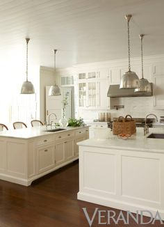 Serene off white kitchen by Timothy Whealon featuring double islands (one for prep and one for eating) with matching nickle pendants overhead. A kitchen made to entertain