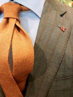 Tan suit with rust stripes and solid orange tie from Isaia.
