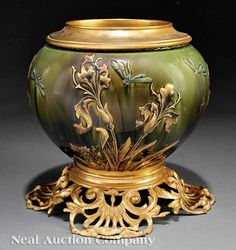 A Luneville Art Pottery Bronze-Mounted Jardiniere, late 19th c., molded insert, boldly scrolled base decorated with irises and dragonflies, glazed in greens, browns, and gold, height 11 1/4 in., diameter 10 1/4 in