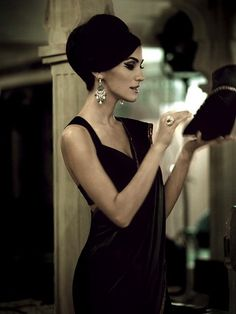 Before starting her rounds of elegant evening galas, Nora upgrades her wardrobe and makeup in a hotel ladies room