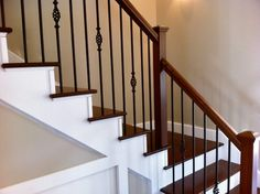 Beautiful stairway with dark steps, white risers, black wrought-iron balusters and cherry railing.
