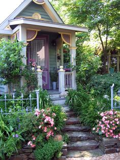 Sweet ❤  I like the stone steps leading towards it, and the fence, and the roses in front of it, and its little porch, and its colors.