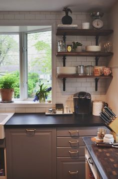 My IKEA Bodbyn grey kitchen. Karlby walnut countertops painted with chalkboard paint then waxed, open shelving with un-stained waxed walnut shelves, wrought iron brackets and brass fasteners, matte white subway tile, grey grout, Schoolhouse Electric sconces, brass hardware, vintage Persian rug, pop art...all DIY!