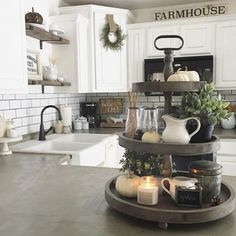 Concrete counter tops. Backsplash. White cabinets. Exposed shelving with stained wood. Apron sink. Iron accents.