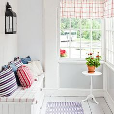 A narrow three-season room benefits from seating that's tailor-made for the space. Drawers hold outdoor decor; a colorful cushion, throw pillows, and a patterned rug offer a comfy place for a private moment. | Photo: Devis Bionaz/GAP Interiors | thisoldhouse.com