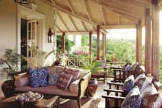 At an estate on the Caribbean island of Mustique designed by architect Luboš Kráčmar with decorator Grant White, the airy veranda of includes furniture from Bali and an assortment of printed pillows. The doorway and quoins are made of concrete treated to resemble coral.