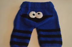 Fun pair of knit pants for babies and toddlers, Cookie monster style shown here but can be made with any characters, sports team logos or designs you want; feel free to start a conversation to discuss what you want.     These pants are completely handmade and knit using a soft acrylic yarn that makes washing them easy, they are soft and move well with active babies. They have an elastic waist that is covered with fleece so as not to cause any irritation. The legs have a slight ribbed cuff…