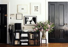 love this so much: the white walls, black doors, wooden floors, framed art and giant vase of lilacs