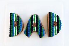 The letters D A D cut out of cake and with blue and green piped buttercream.