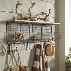 Mesh Entryway Organizer from Wayfair Canada Corral hats, sunglasses, scarves, and more in this wire mesh wall rack, featuring four cubbies, four hooks, and a wood-planked top.