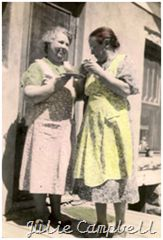 Two of my great-grandmothers sharing a taste of something yummy on the back porch...love the aprons!