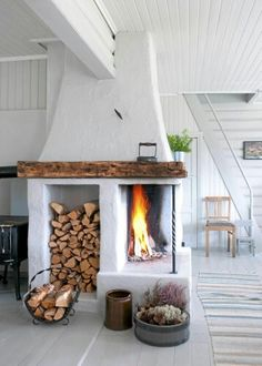 So unique and absolutely Skandinavian - white quarter fireplace, wood storage