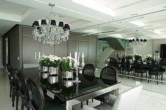 Mesa com tampo em vidro preto, cadeiras pretas e espelho bisotado na parede.