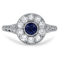 THE REMY RING : This platinum Art Deco ring showcases a round natural sapphire in a bezel setting surrounded by a scintillating halo of ten old European cut diamond accents. Intricately pierced details on the gallery and shoulders add to the floral-inspired look of this piece (approx. 0.62 total carat weight).