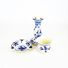 A timeless group of original 20th century hand painted Delft blue ceramics from Holland. The group comprises of a beaker (7cms / 2.75inches by 8cms / 3.1inches) a trinket / ashtray (12cms / 4.7inches diameter), and chamber-stick (15cms / 6inches high).  This famous Dutch pottery with its vibrant unfaded blues complement each other extremely well and would make a beautiful addition to any home décor scheme whether used in a lounge or as a trinket tray / light in a bedroom.  All three pieces…