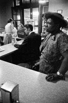 """Photographs by Alfred Wertheimer - """"July 4, 1956. Chattanooga railroad station. This is a segregated lunch counter. This woman got suspicious of me, ordered a tuna fish sandwich and walked in front of my lens. She then moved when she picked up her sandwich to go to the waiting room to eat.""""   Elvis Presley in background"""