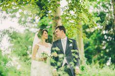 Bride & Groom wedding portrait, through summer green leaves, under trees. Done Arms, Wykeham, Scarborough, North Yorkshire.