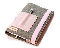 Die Buchhülle/Kalenderhülle eignet sich für das *Format A5* und wurde aus Filz und Leder genäht.  Im vorderen Bereich befindet sich ein kleines Fach für drei Stifte. Die Buchhülle verfügt...