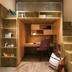 Quarto com cama elevada sobre mesa de estudos. Escada de acesso à direita e estante à esquerda da mesa, tudo em madeira.