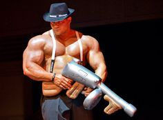 A bodybuilder enters the stage with a toy gun at the FIBO Power in Essen, Germany, Friday, April 20, 2012. The FIBO is a leading international trade show for fitness, wellness and health. (AP Photo/Martin Meissner)