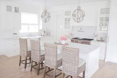 These wicker barstools, from Restoration Hardware, add texture and warmth to this crisp white kitchen. Great choice!
