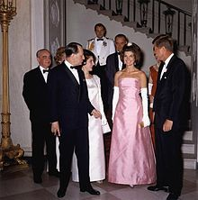 First Lady Jacqueline Bouvier Kennedy, President John F. Kennedy, André Malraux, Marie-Madeleine Lioux Malraux, Lyndon B. Johnson and Lady Bird Johnson having just descended White House Grand Staircase on their way to a dinner with the French cultural minister, April 1962. The First Lady wears a gown designed by Oleg Cassini[106]