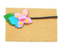 Pink butterfly headband sitting on a leaf