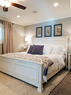 The new master is painted in soft gray and decorated with blue and purple accents. The window treatments employ both wood shutters and drapes, and the wood bed frame is painted in white and given a lightly distressed finish.
