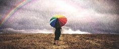 Día de la Tierra 22 de Abril. Una mujer con un paraguas camina bajo la lluvia en un campo, al fondo se ve un arco iris. Foto OMM
