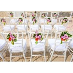 Bright blooms in tropical arrangements are tied to wedding chairs ~ perfect for a beach wedding ~ Centara Grand Beach Resort Phuket