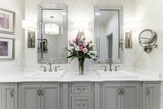 Soft gray cabinetry and papered walls layer this bathroom with transitional elegance. Tiered, self-framed mirrors echo the lines of the square sinks. Contemporary sconces and a wall-mounted mirror add convenience and function.