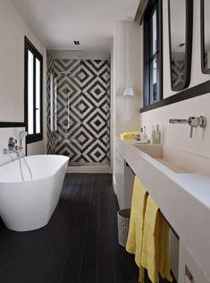 Belle salle de bain dans le blanc, noire, gris et jaune. Très joli!