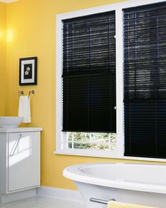 Black window treatments, like these Hunter Douglas Brilliance Pleated Shades create a tailored effect when paired against bright yellow walls.