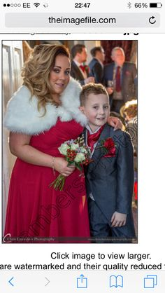 Beautiful bridesmaid Sarah and her son in one of our bridesmaid dresses holding a posie of roses and winter berries with willow.
