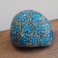 Stone blue flowers Decorated with acrylic paint and protected with transparent water. Dimensions 7 x 5.5 cm. about Weight 210 gr. The stone remains standing alone, given its panettone, so it can be exposed wherever you want, and is decorated all around, always with blue flowers. Very nice even exposed in the garden, or in a large vase of flowers which comes as colors of the stone