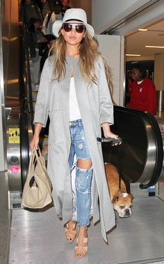 Chrissy Teigen in distressed denim and a floor-length coat, accessorized with strappy nude heels and a floppy hat