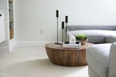 Centerpiece, Natural Brown Round Slab Wood Low Coffee Table With Books And White Elephant Sculpture And Black Iron Candleholders And Brown Ceramic Bowl For Plants U Shaped Light Grey Fabric Sofa Set With Pillows: Living Room Accessories Low Coffee Table, Living Room Accessories, Fabric Sofa, Grey Fabric, Wood Slats, Cocktail Tables, Sofa Set, Built Ins, Decoration