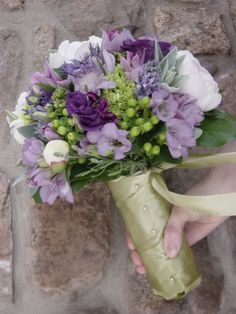 Lavender flowers and even shades of purple are incredibly wonderful to design with. Some color pallets are very limiting with only a few different types of blossoms available but not this color.  Almost all flowers come in some shade of lavender or purple. This gives the bride lots of options and flower choices. This bouquet …
