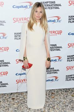 Sienna Miller stunned in a simple white cape dress and red lip clutch