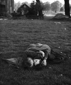 An American soldier kissing his English girlfriend on the lawn in Hyde Park, one…
