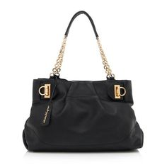 This Salvatore Ferragamo tote is made from gathered black leather with gold-tone hardware. Details include two chain-linked handles and a magnetic snap closure. The interior is fully lined with two open pockets and two zippered pockets. Carry this style on the forearm or over the shoulder.