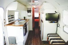 Painted white camper interior, butcher block countertop, wood floors, add pop color