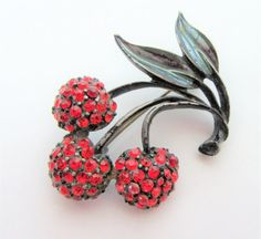 Fabulous red cherry brooch set with red rhinestones on a black japanned background. Highlighted by g