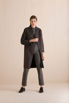 Grand, a double face gray and green pure wool coat. This coat has raglan sleeves, a wid fit and an asymmetrical neckline with no lapels. Galo total look from the Cortana prêt-à-porter collection, in brown and green checked wool. A masculine shirt with a mandarin collar, with the matching high waisted slim fit pants with a side zip. Ready-to-wear with an artisanal touch, crafted in Barcelona.