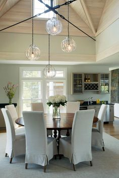 Varied fabrics and textures in shades of beige come together to provide a look of beauty and feeling of peace in this open dining space. A chandelier with 4 lamps hangs above the table, which is surrounded by upholstered chairs.