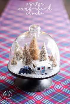 DIY Winter Wonderland Cloche. Make simple and festive winter crafts to decorate your home with this holiday season. All you need is a cloche, fake snow, some miniature winter items, and Elmer's CraftBond Hot Glue!